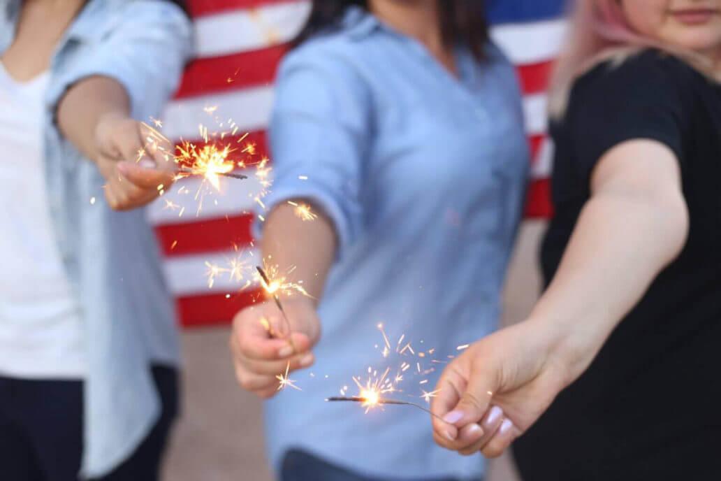 three women holding sparklers