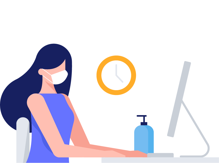 A woman sits at a desk next to hand sanitizer and types on a computer while wearing a mask.